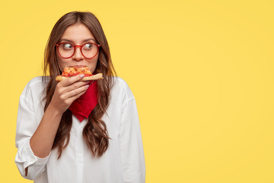 Satisfied Caucasian model eats delicious pizza indoor, has lunch, wears optical glasses, white shirt and red bandana, stands against yellow background with free space for your slogan or text