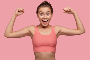Photo of strong cheerful young sportswoman shows biceps at camera, works on muscles in gym, wears casual top in one tone with background, has healthy perfect body, being amazed. Sport concept