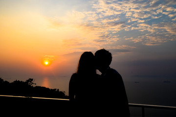 Silhouette couple on the view point to watch sunset