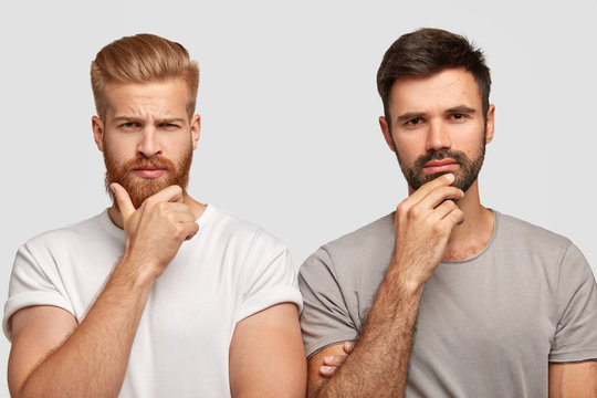 Photo of serious two men hold chins, dressed in casual t shirts, model against white background, being deep in thoughts, find way out of problem. Ginger man and his friend pose indoor at studio
