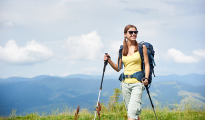 Attractive happy woman tourist hiking in Carpathian mountain trail, walking on grassy hill, wearing backpack, sunglasses, using trekking sticks, enjoying summer day. Outdoor activity, tourism concept
