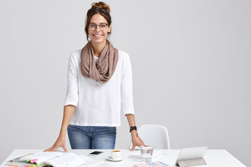 Satisfied intelligent female tutor wears white jumper and jeans, keeps hands on table, ready to give private lessons, drinks coffee, stands against white background. Woman works freelance at project