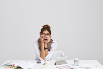 Depressed woman has troubled facial expression, keeps hands on cheeks, has difficulties with making marketing review, looks desperately upwards, reads book, uses tablet, isolated on white wall