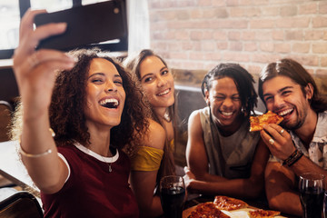 Mulltiracial friends taking selfie at pizza restaurant