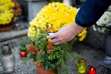 man hands lighted candle and putting on the grave, halloween