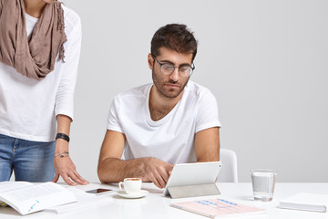 Serious Caucasian man worker thinks on solving problem for project, works on touch pad, drinks coffee, his female assistant stands near, cooperate to prepare for seminar, isolated on white background