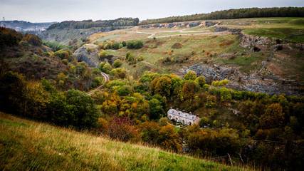 Old stone cottages in the bottom of a dale surrounded by autumn trees on a cloudy day. Taken in the Derbyshire Dales.