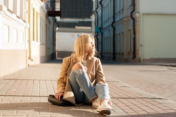 Young european girl dressed in fashionable ripped jeans and sweater posing outside on a sunny autumn day