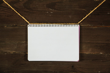 Paper mock up old notebook on a rope on a black wooden board. Place for text. Copy space. Place for announcements.