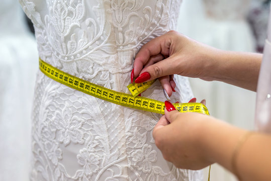 Measuring yellow tape with female hands and wedding dress