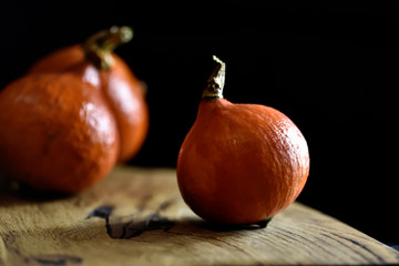 orange mûr brillant, citrouilles Hokkaido, sur une planche de bois sur un fond noir