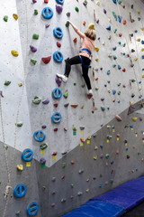 Chubby pretty Caucasian girl climbering artificial rock-climbing walls