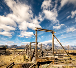 Western cattle corral with Teton mountains and clouds in the sky