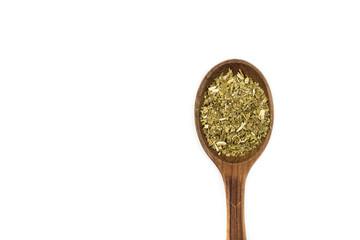 Yerba Mate Tea on wooden spoon isolated on white. Dried yerba mate tea powder.