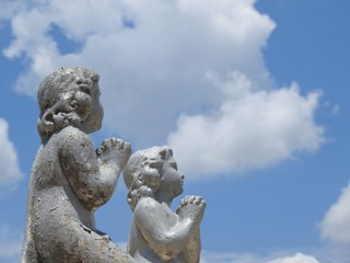 Scene in a cemetery: two children's stone statues with their hands together, praying. In the background, clear blue sky with clouds.
