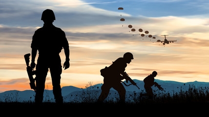 Silhouette of soldiers at sunset watching the launch of paratroopers