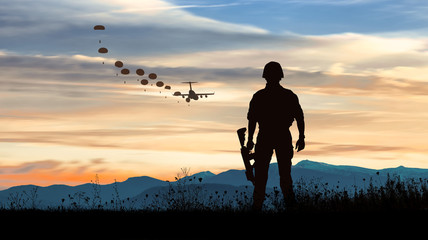 Silhouette of soldier at sunset watching the launch of paratroopers