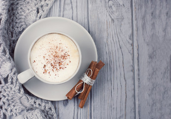 Gray cup of coffee cappuccino, sticks of cinnamon and knitted scarf on a gray background. Top view, copy space