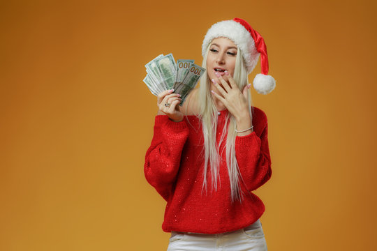 Pretty caucasian young happy woman in red Santa hat holding gift box and money banknotes on yellow background. Won cash in lottery. New Year holiday 2019 concept.