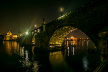 Night view of illuminated stone Charles bridge with statues, street lamps, church of St Francis Assisi, view under bridge across Moldau river towards National theatre of Prague, Czech republic, Europe
