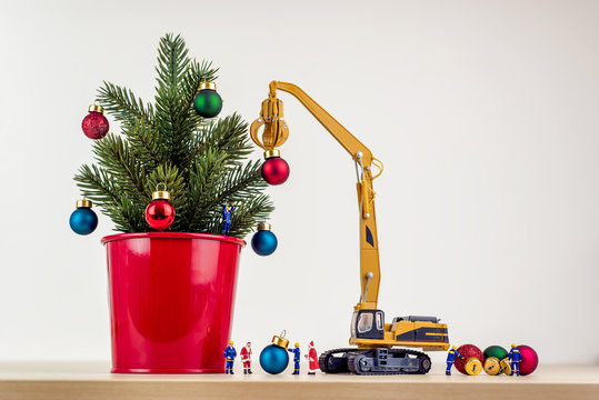 Miniature workers decorating christmas tree