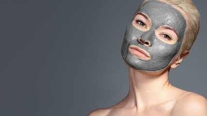 Beautiful Woman Applying Black Facial Mask. Beauty Treatments. Spa Girl Apply Clay Facial mask on grey background