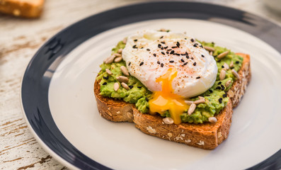 Close up food photography of an avocado toast with poached egg and sesame seeds. Breakfast, lunch, brunch, light dinner dish meal, vegetarian food, healthy eating concept.