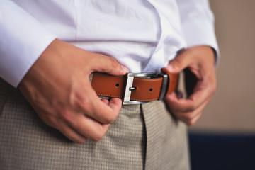 man adjust his belt of elegant suit. getting ready concept.