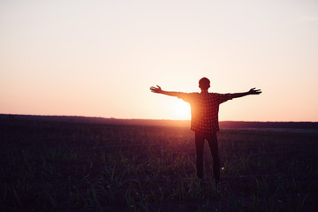 Feel good freedom concept. Happy young asian man enjoying freedom with open hands in farm and sunset sky background.