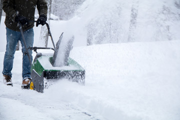 Snowblower in action during a snowstorm in the Northeast, maintaining driveway during Nor'Easter blizzard