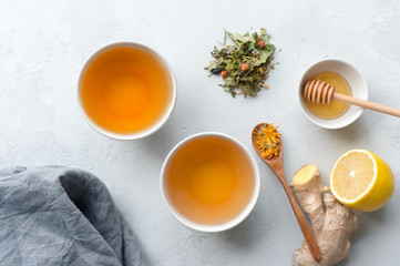 Herbal tea cups on concrete table. Treat cold and flu. Lemon, ginger, honey and herbs. Top view.