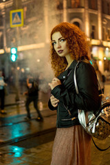 Young red-haired girl smokes an electronic cigarette. Lonely walk on streets of night city. Nicotine Cigarette. Wet asphalt after rain.