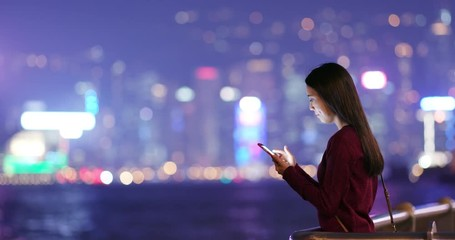 Wall Mural - Woman look at mobile phone in city at night
