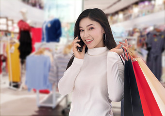 woman talking on smartphone and holding shopping bags at mall