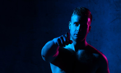 Neon light portrait of sexy smiling man muscular body pointing finger on dark