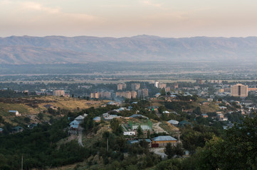 Summer view on plateau with the Dushanbe in Tajikistan. A sparse buildings among a trees and a mist on mountains on background.
