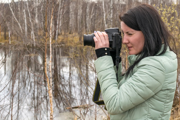 A girl in a warm jacket in the spring taking pictures of nature near the swamp