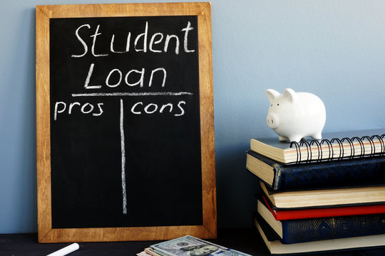 Student loan pros and cons handwritten on a blackboard.