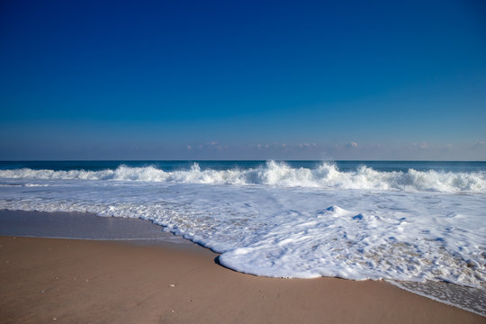 Smooth sand beach with tropical ocean and clam waves with blue sky on sunny day in Summer - Ocean City, Maryland USA