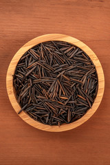 Black wild rice, shot from above in a wooden bowl on a dark rustic background with a place for text