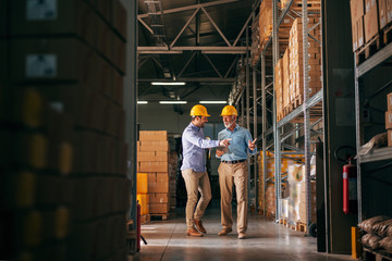 Workers walking in storage and pointing at boxes. In hands folder and tablet, on heads helmets.
