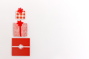 Pile of three wrapped christmas gifts in red paper