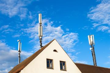 Mobilfunkmasten auf einem Hausdach in Deutschland