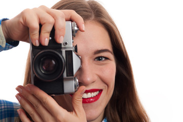 Close-up Portrait of young charming positive woman photographer with vintage camera in casual clothes on white background