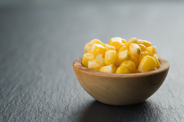 canned corn kernels in woob bowl on slate background
