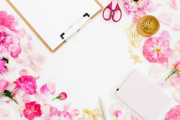 Composition with clipboard, notebook, accessories and pink flowers on white background. Flat lay, top view. Copy space