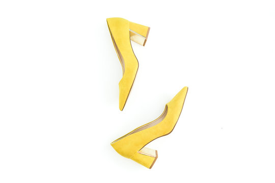 Women fashion. Female concept with yellow shoes on white. Flat lay, top view.