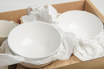 Photo Stands Ready meals Clean white dishes in paper packed in a cardboard box. Concept relocation.