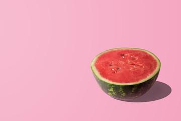 Sliced watermelon on pastel pink background. Minimal fruit concept.