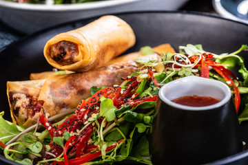 A plate of three spring rolls, green salad and chilli sauce
